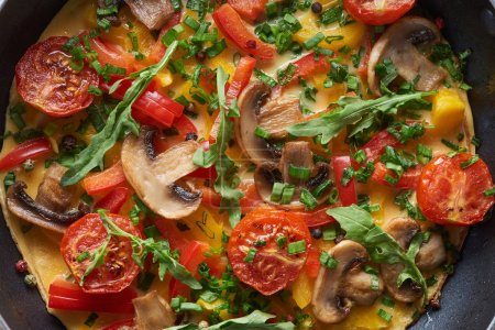 Photo for Top view of homemade omelet with mushrooms, tomatoes and greens - Royalty Free Image