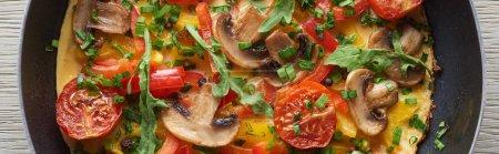 Blick von oben auf hausgemachtes Omelett mit Pilzen, Tomaten und Gemüse in der Pfanne