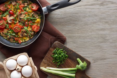 Photo for Top view of delicious homemade omelet in frying pan with ingredients on wooden table - Royalty Free Image