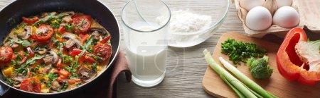 Photo pour Omelette maison dans une poêle à frire avec lait, farine, œufs et brocoli sur la table - image libre de droit