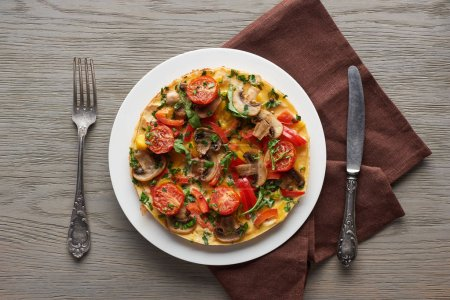 Photo for Homemade omelet with vegetables on wooden table with fork, knife and napkin - Royalty Free Image