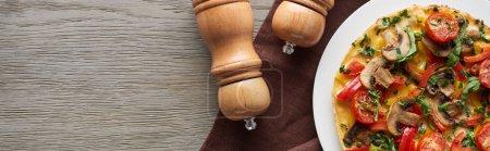 hausgemachtes Omelett mit Gemüse auf Holztisch mit Pfeffer und Salz