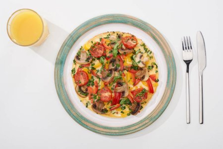 Photo for Top view of plate with homemade omelet for breakfast on white table with glass of juice, fork and knife - Royalty Free Image