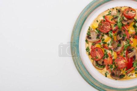 Photo pour Vue du dessus de l'assiette avec omelette savoureuse aux tomates, légumes verts et champignons pour le petit déjeuner sur table blanche - image libre de droit