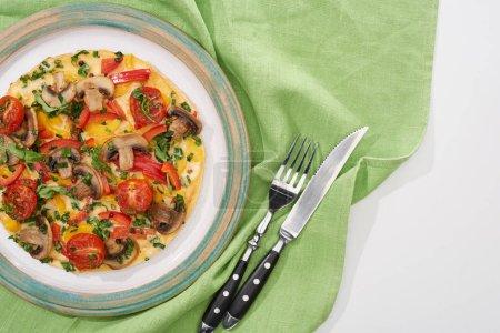 Teller mit hausgemachtem Omelett zum Frühstück auf weißem Tisch mit Serviette, Gabel und Messer