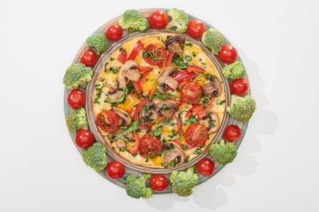 top view of homemade omelet on plate with fresh tomatoes and broccoli