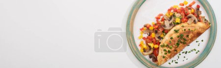top view of plate with homemade wrapped omelet with vegetables on white table