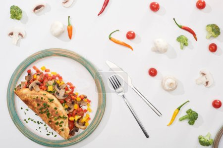 Photo for Top view of plate with homemade wrapped omelet with vegetables on white table with ingredients, fork and knife - Royalty Free Image