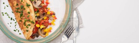 Photo for Top view of plate with wrapped omelet with vegetables on white table with fork and knife - Royalty Free Image