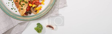 Photo for Top view of yummy wrapped omelet with vegetables on plate with ingredients - Royalty Free Image