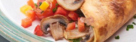 Nahaufnahme von eingewickeltem Omelett mit Champignons und Paprika auf Teller
