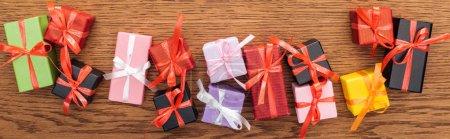 Photo pour Vue du dessus de petites boîtes-cadeaux décoratives avec rubans sur fond en bois, vue panoramique - image libre de droit