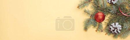 Foto de Top view of christmas tree branch with bauble on yellow background, panoramic shot - Imagen libre de derechos