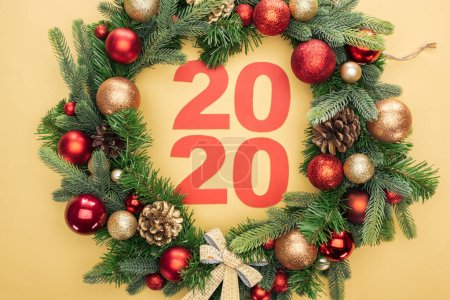 Photo pour Top view of paper 2020 numbers in christmas wreath with baubles on yellow background - image libre de droit