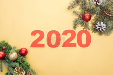 Photo for Top view of paper 2020 numbers near christmas tree branches with baubles and cones on yellow background - Royalty Free Image