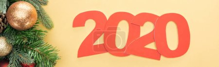 top view of paper 2020 numbers near christmas tree branch with baubles on yellow background, panoramic shot