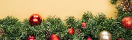 Photo for Top view of christmas tree branch with red and golden baubles on yellow background, panoramic shot - Royalty Free Image