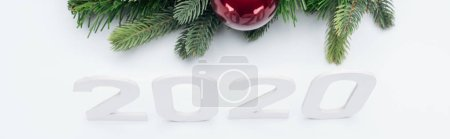 Foto de Top view of paper 2020 numbers near Christmas tree wreath with bauble on white background, panoramic shot - Imagen libre de derechos