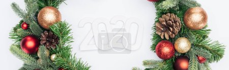 top view of 2020 numbers in Christmas tree wreath on white background, panoramic shot