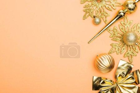 Photo pour Vue du dessus de la décoration de Noël dorée sur fond orange avec espace de copie - image libre de droit