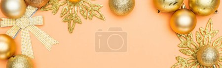 top view of golden Christmas decoration on orange background with copy space, panoramic shot