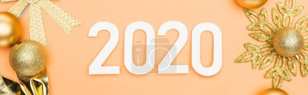 Photo for Top view of white 2020 numbers near golden christmas decoration on orange background, panoramic shot - Royalty Free Image