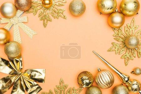 Foto de Frame of golden christmas decoration on orange background with copy space - Imagen libre de derechos