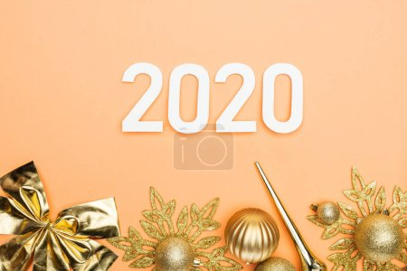 Photo for Top view of white 2020 numbers and golden christmas decoration on orange background - Royalty Free Image