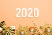 top view of white 2020 numbers and golden christmas decoration on orange background