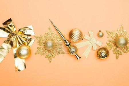 Foto de Top view of festive golden christmas decoration on orange background - Imagen libre de derechos