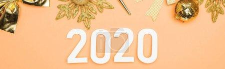 Photo pour Vue du dessus des chiffres blancs 2020 près de la décoration de Noël dorée sur fond orange, vue panoramique - image libre de droit
