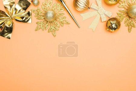 Foto de Top view of festive golden christmas decoration on orange background with copy space - Imagen libre de derechos