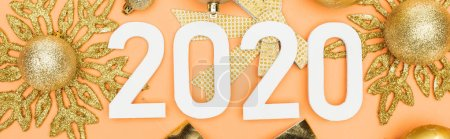 top view of white 2020 numbers on golden christmas decoration on orange background, panoramic shot