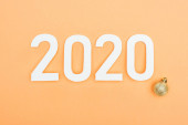 top view of white 2020 numbers near golden christmas bauble on orange background