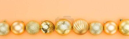 Foto de Top view of golden christmas baubles in row on orange background, panoramic shot - Imagen libre de derechos