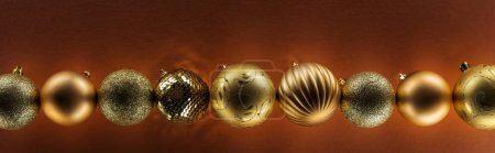 top view of golden christmas baubles in row on dark background, panoramic shot