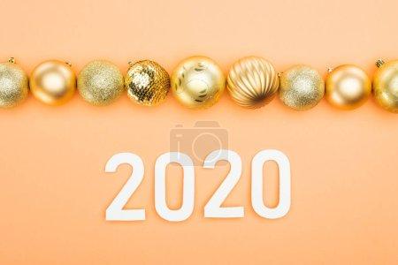 Foto de Top view of white 2020 numbers near golden christmas baubles on orange background - Imagen libre de derechos