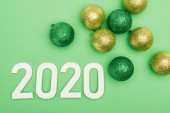 top view of white 2020 numbers near christmas baubles on green background