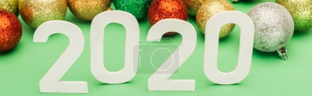 Photo for White 2020 numbers near multicolored Christmas baubles on green background, panoramic shot - Royalty Free Image