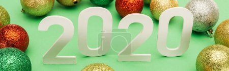 white 2020 numbers near multicolored Christmas baubles on green background, panoramic shot