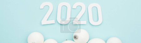 Photo for Top view of white 2020 numbers near Christmas baubles on light blue background, panoramic shot - Royalty Free Image