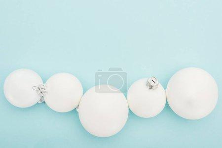 Foto de Vista superior de las bolas blancas de Navidad en fondo azul claro con espacio para copiar. - Imagen libre de derechos