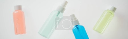 panoramic shot of colorful bottles with liquids on white background
