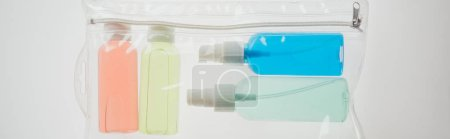 Photo for Panoramic shot of colorful bottles with liquids in cosmetic bag on white background - Royalty Free Image