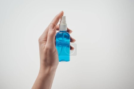 Photo pour Vue recadrée de la femme tenant bouteille avec du liquide sur fond blanc - image libre de droit