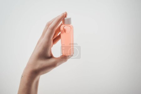 cropped view of woman holding bottle with liquid on white background