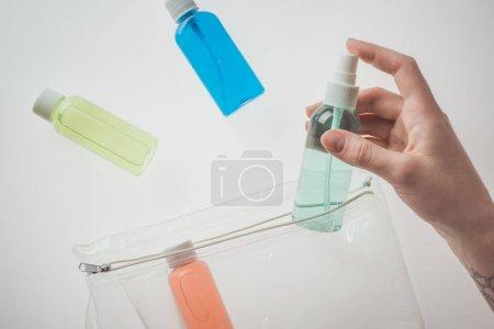 abgeschnittene Ansicht einer Frau mit Flasche mit Flüssigkeit auf weißem Hintergrund