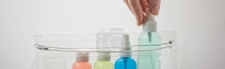 Photo for Panoramic shot of woman putting bottle with liquid to cosmetic bag on white background - Royalty Free Image