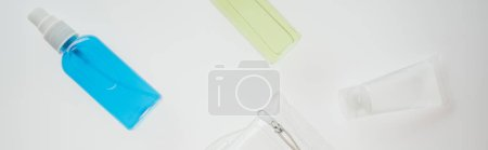 panoramic shot of cosmetic bag and bottles with liquids on white background