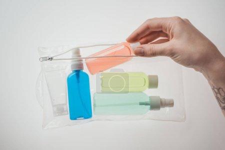 Photo pour Vue recadrée de la femme mettant bouteille avec du liquide pour sac cosmétique sur fond blanc - image libre de droit